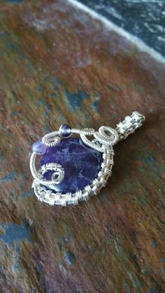 Amethyst  button bead  wrapped with  sterling silver wire (pendant )by Tamara's Treasures.