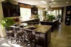 Dark wood cabinets and lots of natural light combine nicely in this welcoming kitchen  (Kitchen-Design-Ideas.org)