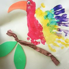 Parrot Footprint with handprint wings  Materials Needed:  - Paints  - Orange & brown construction paper  - Green leaves (gathered from nature walk)  - Googley eyes #diy #crafts #wedding www.BlueRainbowDesign.com