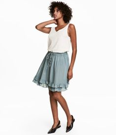 Dusky green. Short circle skirt in thick, woven cotton fabric. Elasticized drawstring waistband and seam at hem with double flounce.