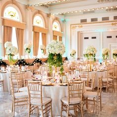 Gold candelabras were topped with rounded white-and-green arrangements. Ivory linens and gold chairs finished the look. Giffin's Floral & Event Design. Westin Columbus.     Love these center pieces! We're doing something similar for our wedding with Eiffel Tower Vases.