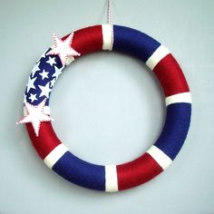 "American Yarn Wreath. 14"" Patriotic wreath. Red, white and blue stripes with white felt stars."