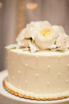 Simple white cake with pretty flowers. I don't want polkadots. A couple tiers with pretty open roses would be lovely.