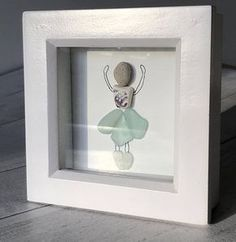 A unique sea glass art of a ballet dancer The dancer is made from beautiful frosted sea glass and sea pottery. Her skirt is three beautiful pieces of Scottish aqua sea glass whilst her top is a lovely fragment of patterned purple beach pottery. Her little ballet shoes are made from aqua #seaglassart