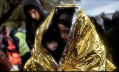 """afp-photo: """" GREECE, LESBOS : Children huddle inside emergency blankets as they arrive with other refugees and migrants on the Greek Island of Lesbos on October 2015 after crossing the Aegean sea."""