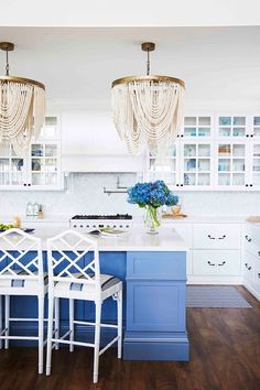 A Hamptons farmhouse kitchen with blue island bench and beaded chandeliers. Hamptons Kitchen, Hamptons House, The Hamptons, Blue Chandelier, Beaded Chandelier, Chandeliers, Kitchen Design, Kitchen Decor, Kitchen Ideas