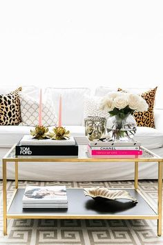 Contemporary living room boasts a white slipcovered sofa by Ikea lined with leopard pillows and gold pillows by Caitlin Wilson Textiles facing an Ikea Vittsjo Nesting Table painted gold atop a gray Greek key rug.