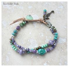 """Colorful two strand asymmetrical bracelet with Russian amazonite faceted nugget, artisan lampwork, sterling silver, seaglass button, and natural leather link with brass seahorse and stacked crystal charms. -Fits a 6.5""""-7"""" wrist, can be adjusted, just leave a note at checkout."""