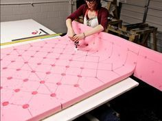 "Pad the headboard with 2""-thick firm density foam. Since the headboard is larger than a typical slab of foam, use foam and fabric spray adhesive to glue multiple pieces of foam together. Draw the diamond grid again on the foam. Use a hole-saw drill bit to remove the foam over every hole. From the buttons on the outer edges, draw lines straight out to the edges of the foam. In the curved section between the headboard and wings, it may be necessary to reduce the spacing of the buttons since…"