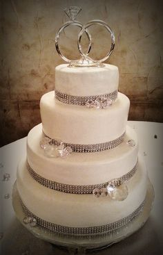 "- Simple & chic ""Bling"" themed four (4) tier wedding cake: 14"" spiced carrot cake with caramel fill, 12"" WASC with raspberry fill, 10""- Butter cake w/ french vanilla fill, & 6"" topper- spiced carrot... Butter cream Icing"