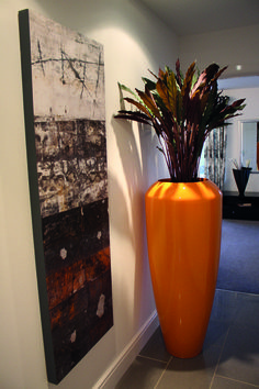 Orange Dune planter used to compliment piece of art on wall.