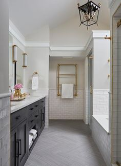 Gray herringbone bath floor tiles bring visual interest to a long bathroom design along with white marble vanity countertops accented with an Arteriors Piedmont Vase, white glazed bath tiles and brass fittings.