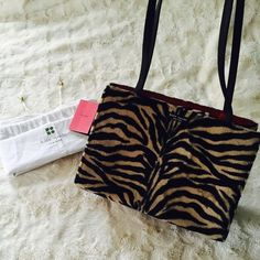 KATE SPADE♠️ Animal Print Tote bag Animal Print Tiger / Zebra like print faux fur.                        Red interior. Black leather straps. Magnetic closure.                                                                 Zippered pocket on the inside.                                                  Few minor marks inside, hardly noticeable.                           Comes with booklet/ gold bead dust bag !                                                         Great condition. kate…