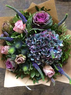 A mix of memory lane and amnesia roses with hydrangea, veronica, blue thistle and ornamental cabbages made by Alice