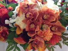 Mix it up! Cymbidium orchids paired with orange dahlias and orange callas make a very cool bridal bouquet