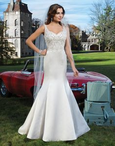 Justin Alexander wedding dresses style 8739 Regal satin trumpet with a heavily beaded pearl and crystal V-neckline.  The back of the gown is finished with a plunging deep V-backline, a jeweled tie,  and regal satin and crystal buttons extending to the end of the chapel  length train.