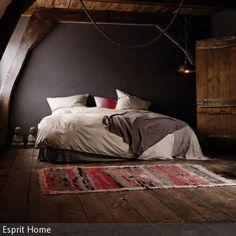 Erdige Brauntöne strahlen eine warme Atmosphäre aus: Die braune Wand, die Dielen und Tür aus Naturholz sowie walnussfarbige Holzbalken erwecken einen  …