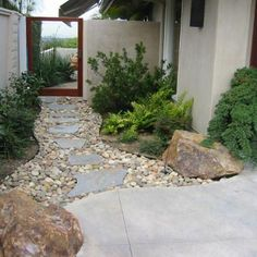 A simple rock & stone walk-way in between the house and garage to the backyards gate