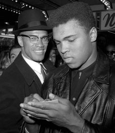 In this March 1, 1964, photo, heavyweight boxing champion Muhammad Ali, right, is shown with black muslim leader Malcolm X outside the Trans-Lux Newsreel Theater in New York, after viewing the screening of a film about Ali's title fight with Sonny Liston. (AP Photo/File)
