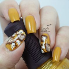 Golden brown colored leaf nail art design. The combination of the golden brown base color with the white and chocolate brown leaves makes a perfect pairing for the nails to look luxurious and eye catching.