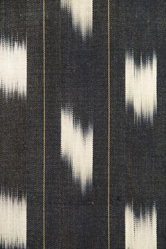Ooti Cotton Fabric Black Cotton fabric with tie died white Ikat design and thin gold stripe. Suitable for Curtains, Soft furnishings and General Domestic Upholstery.