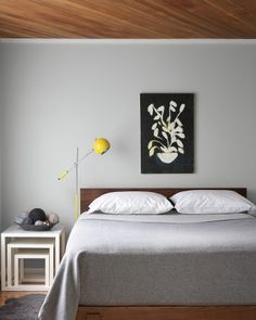 A wood ceiling, installed by the original owners, gives a warm touch to the master bedroom, as do the walls, which are painted a pale blue-gray. Everything this homeowner added to the room has simple lines, from the bed to the square nesting tables; she painted the canvas, and the bedding is from Lands' End.