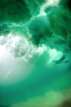 Green ocean. Surfer duck diving under the waves.