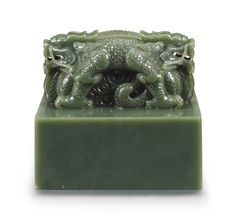 A MASSIVE SPINACH-GREEN JADE 'DRAGON' SEAL WITH MANCHU AND CHINESE INSCRIPTIONS QING DYNASTY of large square form, surmounted by a superbly articulated pair of addorsed dragons, each powerfully depicted with eyes bulging and nostrils flaring above curling whiskers and jaws bearing sharp fangs, the scales and flowing mane meticulously incised, the two scaly bodies tightly intertwined and crouching on the haunches, pierced through the centre with an aperture, the seal face carved with two…