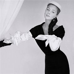 Model wearing black dress and white hat by Hattie Carnegie, with white bow knot satin sleeves by Balenciaga.