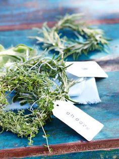 Kräuter aus Salbei, Thymian und Rosmarin verbreiten ein angenehmes Aroma: Aus einem Kräuterstrauch Zweige schneiden und mit einem Blumendraht zu einer etwa 30 cm langen Rute binden, zum Kreis biegen und mit Draht fixieren. Anschließend auf Papieretiketten einen Begrüßungsspruch stempeln und an den Kranz binden.