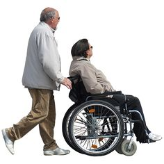 A man endearingly showing his wife around town while she is seated in a wheelchair.