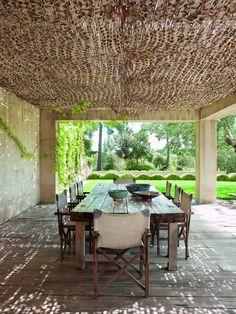 Bajo una red de camuflaje militar, en la pérgola-cenador, gran mesa de madera de ciprés, diseñada por Bastidas.