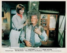 Elsa Martinelli and John Wayne in Hatari.   -Give me a hand with this, Dallas. - Do you want your door closed? - No, I can't breathe.