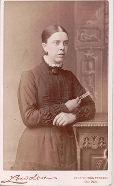 Mourning CDV 04: This young woman is holding a CDV of a man, indicating that she is mourning his presence. She is also wearing a black brooch and earrings so is probably in half mourning.