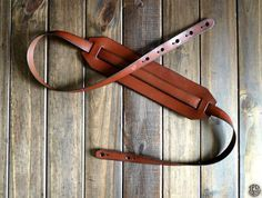 This handmade leather guitar strap is cut from rugged 6-7oz bridle leather. The two-piece folk design has keyholes notched into both ends for a wide adjustment range. The main strip is 1 thick, and It has a removable shoulder pad for added comfort. This strap is compatible with most electric and acoustic guitars - It can also be personalized with a custom message: names, initials, poetry, etc. The strap shown above is finished in russet, and accented with a solid line trim.  These straps are…