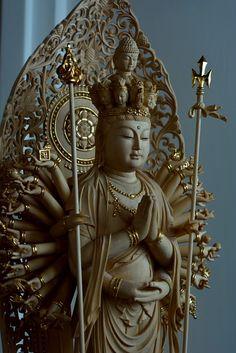 仏像彫刻原田謹刻 千手観音立像(せんじゅかんのんりゅうぞう) 【千手千眼観自在菩薩】 限りない慈悲を表す菩薩で,千の慈悲の眼と千の慈悲の手をそなえ,生ある者を救うという。千は無量円満を表し、すべてのものを同時に見,同時に救う働きをもつ。延命・滅罪・除病の功徳があると信じられ,日本では奈良時代から信仰される。二十八部衆という大眷属を従え、これらは礼拝者を擁護するという。 ◆総高60㎝ 白木素地金線 玉眼のお姿です。