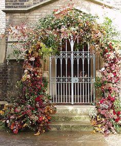 Gorgeous arch framing iron gate. #wedding #flowers #arch