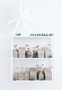 love the idea: advent calendar made out of tiny cardboard houses. adding a little colour and kitsch would be nice though