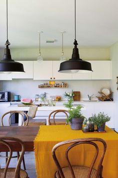Cocina entre moderna y rústica, con mesa de madera y clásicas sillas Thonet, un género mostaza (Zara Home) y latones vintage con suculentas (Otra Sudestada). Las lámparas colgantes tipo industrial son de Iluminación Castelar.