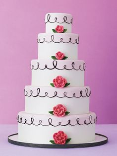 This five-tiered fondant cake with sugar rosettes and calligraphy accents is by Jan Kish–La Petite Fleur