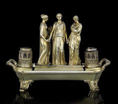 A GEORGE IV SILVER-GILT INKSTAND MARK OF PHILIP RUNDELL, LONDON, 1822, THE DESIGN ATTRIBUTED TO JOHN FLAXMAN, RETAILED BY RUNDELL, BRIDGE AND RUNDELL Oblong and on four foliate scroll bracket feet, the base with moulded borders and foliate reeded handles, the frame set with silver-gilt mounted facet-cut glass inkwell and pounce pot in two bottle holders pierced with anthemia, and centring three classical female figures representing the Cardinal Virtues,