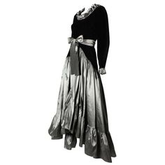 Yves Saint Laurent Velvet & Taffeta Gown. Vintage Yves Saint Laurent gown dates to the early 1980's. Black velvet bodice has a scoop neck and long sleeves, both of which have a taffeta ruffle trim. Drop-waisted asymmetrical skirt is made of gunmetal gray silk taffeta and has a wide ruffle at the hem. Unlined. Side zipper. Waist tie.