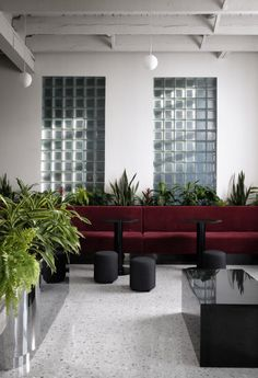 Plants have been strategically planted throughout the minimalist space, creating a calm dark-green contrast against the deep red hues. Exposed Ceilings, Exposed Brick Walls, Architectural Digest, Glass Brick, Of Montreal, Montreal Canada, Terrazzo Flooring, Lesage, Workspace Design