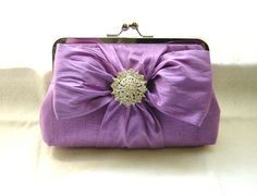 https://flic.kr/p/cnvi45   Lilac Bridal Clutch Purse - Crystal Brooch - Chloe   This beautiful lilac bridal clutch purse is made from a soft lilac dupioni silk with crystal brooch. The clutch is lined in a lavender dupioni silk with a metal frame for closure. A perfect clutch for the special bride on her wedding day.  Colors: *lilac, lavender  Measurements: *Top frame width is 8 inches, bottom of clutch is 9 inches and height is 6 inches  Features:  * 100% soft lilac dupioni silk fabric…