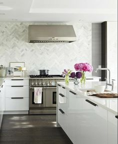 White modern laquer kitchen cabinets with herringbone marble backsplash