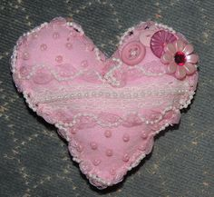 Felt pink heart. Make paper pattern of heart; cut 2 out of felt squares. Embellish one with ribbon, buttons, beads, etc. Sew hearts together, by hand, 1/4 inch from edge (whipstitch),  wrong sides touching, leaving 1/2 inch. Stuff with polyester stuffing. Sew closed the inch. Optional; attach bead or ribbon on edging for more finished look.