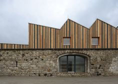 Serrated timber extension transforms stone barn into woodwork facility.