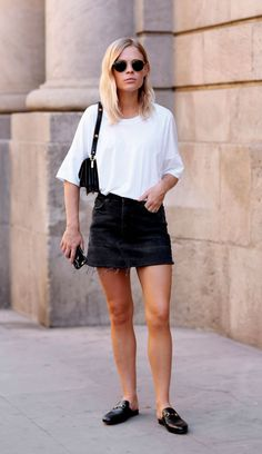 Street style look com camiseta branca, saia jeans e mule.