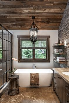 Inside a Stylish Mountain Home on Lake Tahoe Designed by Jeff Andrews - A vintage light from Paris hangs above the tub in the master bathroom, which is accented by a side - Cabin Bathrooms, Rustic Bathrooms, Lake House Bathroom, Lodge Bathroom, Rustic Bathroom Designs, Dream Bathrooms, Bathroom Interior, Bathroom Storage, Vanity Bathroom