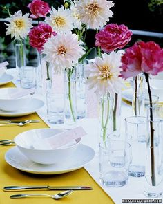 Delicate and airy, this centerpiece composed of single blossoms lets you make the most of a limited group of flowers. Showcase each one -- we used dahlias and garden roses -- in clear glass vessels, such as bud vases, jars, or even drinking glasses. To accentuate the arrangement, set the flowers on a runner with a hue that contrasts the color of the tablecloth.